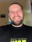 Bild på en leende Andreas på sitt kontor, med Skånes Taltidnings fina t-shirt på sig.